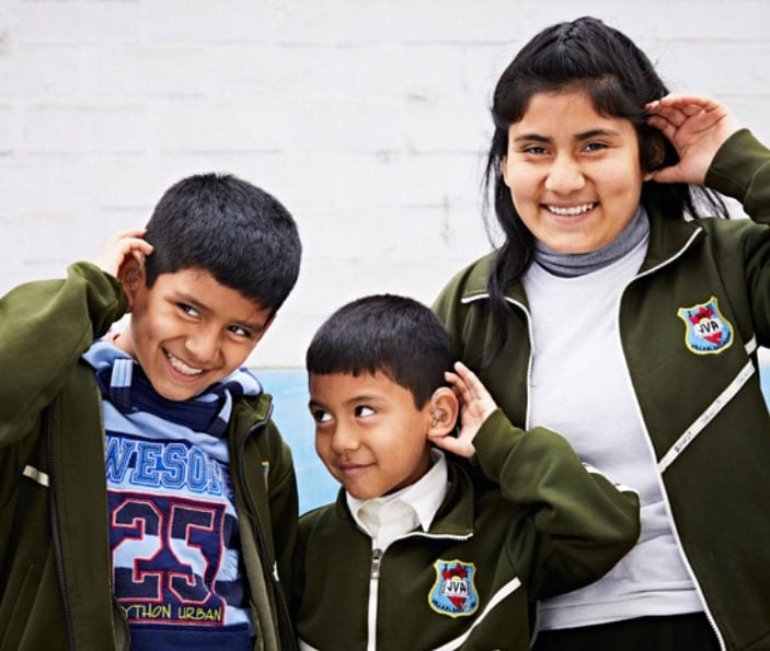 three young children wearing hearing aids