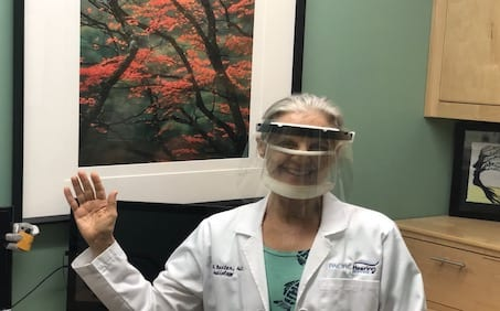 waving audiologist wearing PPE